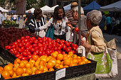 Chicago, Illinois: Horizontal shot of a colorful vegetables' stall and some of its customers in animated conversation at the Chicago Farmer's Market, Daley Sq, The Loop