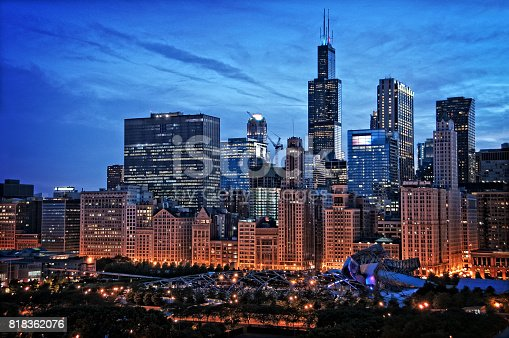 Chicago lakefront skyline cityscape at night by millenium park with a dramatic cloudy sky.