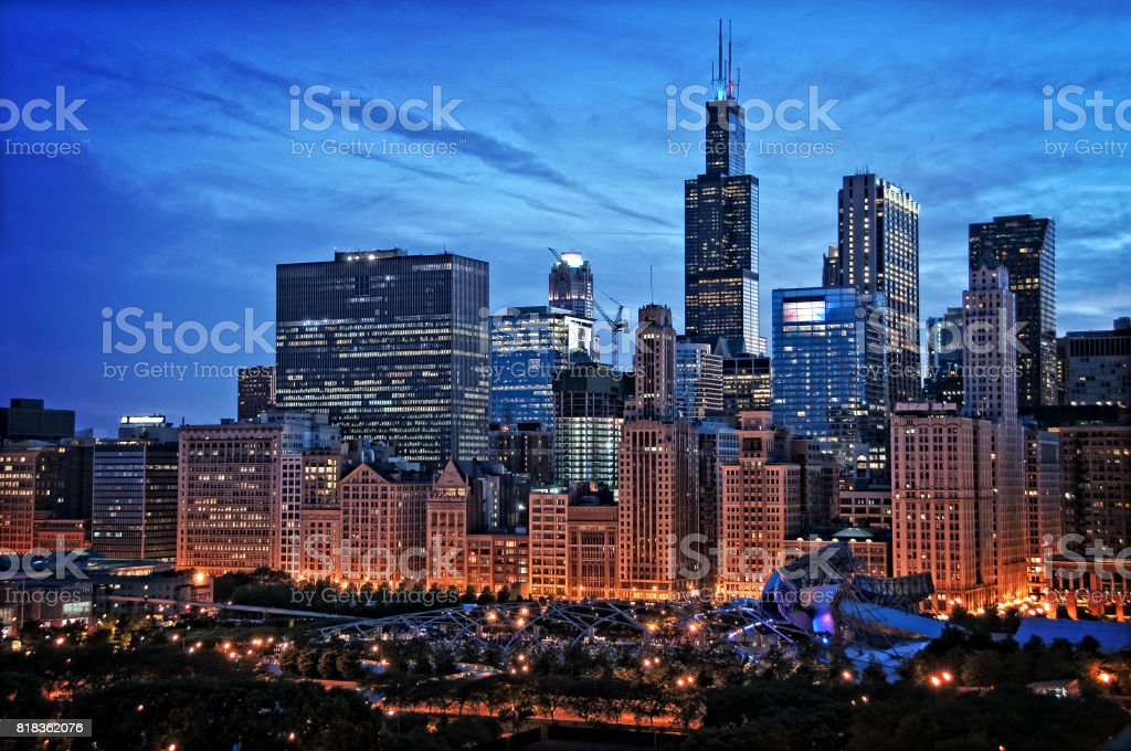 Chicago lakefront skyline cityscape at night by millenium park with a dramatic cloudy sky. stock photo
