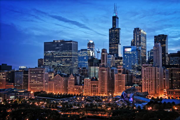 Chicago lakefront skyline cityscape at night by millenium park with a dramatic cloudy sky. Chicago lakefront skyline cityscape at night by millenium park with a dramatic cloudy sky. urban sprawl stock pictures, royalty-free photos & images