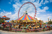 Chicago, United States - August 21, 2015: Fairground with swing ride, carousel and Ferris Wheel at Navy Pier in Chicago. Navy Pier is one of Chicago's main tourist attractions with amusement park. People can be seen walking around the park.