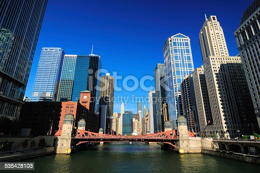 A center view of the Chicago River in Downtown Chicago with a river bridge and towering skyscrapers that line the Chicago River in a canyon-like way.