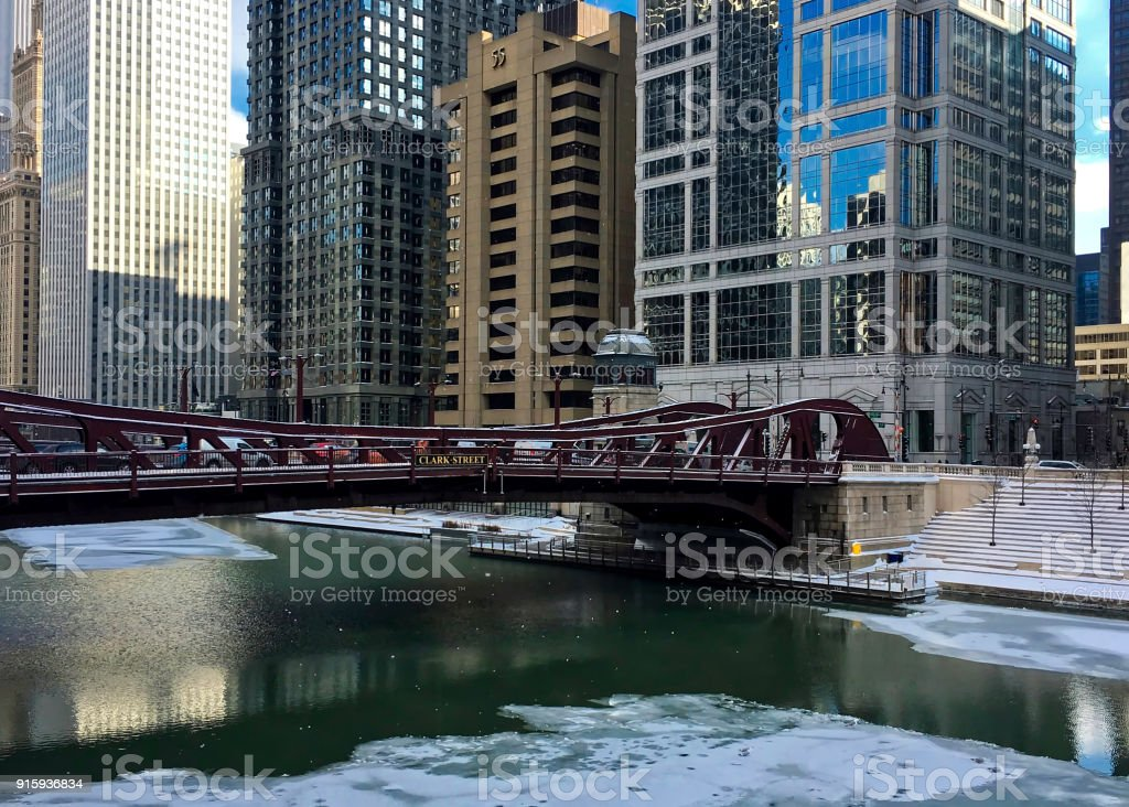Chicago River is frozen and reflecting bridge over it on frigid winter afternoon. stock photo