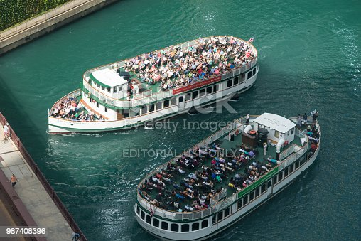 Chicago, USA - Aug 26, 2016: Chicago architectural tour boats full of tourists on the Chicago River in the Loop late in the Day.