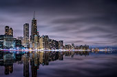 The Chicago skyline and Lake Michigan with colorful clouds at night.