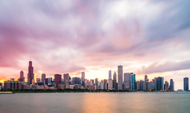 Chicago skyline at sunset with cloudy sky and reflection in water. stock photo