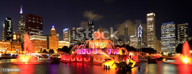 Chicago skyline illuminated at dusk with colorful Buckingham fountain on the foreground, United States of America