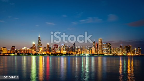 Panorama of Illuminated Cityscape, Skyline of Chicago at Twilight, Night. Modern urban skyscraper lights mirroring in the Lake Michigan water. Long Exposure. Chicago, Illinois, USA.