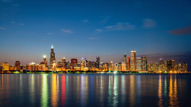 Chicago Skyline Panorama Lake Michigan Reflections at Night Panorama of Illuminated Cityscape, Skyline of Chicago at Twilight, Night. Modern urban skyscraper lights mirroring in the Lake Michigan water. Long Exposure. Chicago, Illinois, USA. chicago stock pictures, royalty-free photos & images