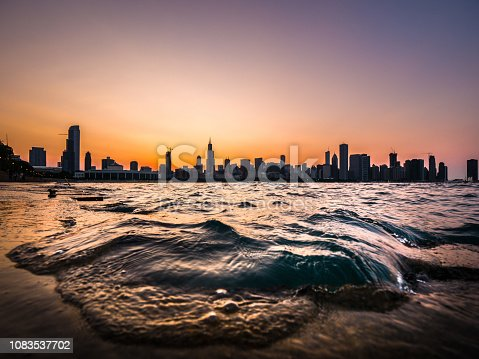 Chicago skyline picture during a beautiful sunset with purple and orange sky above and building silhouettes on the horizon with a wave from Lake Michigan coming up over the concrete shoreline edge.