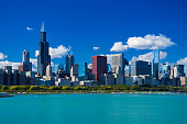 Chicago Skyline featuring the Willis Tower, with a deep blue sky with cumulus clouds in the background, and Grant Park and Lake Michigan in the foreground.