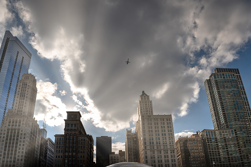 Chicago sunset skyline with airplane flying over modern buildings