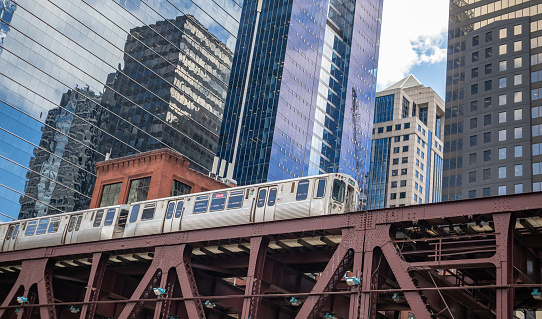 Chicago cityscape, spring day. Chicago train on a steel bridge, downtown on high rise buildings background, low angle view