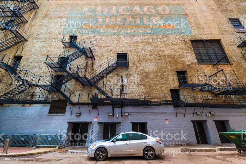 Chicago, USA: Wide angle view of Chicago Theater wall with fire stairs, doors, hand written graffiti sign with orange arrow on blue background, car parked on the street stock photo