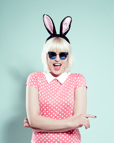 Portrait of excited blonde young woman wearing pink polka dotted dress, sunglasses and rabbit ears headband. Studio shot, one person, turquoise background.
