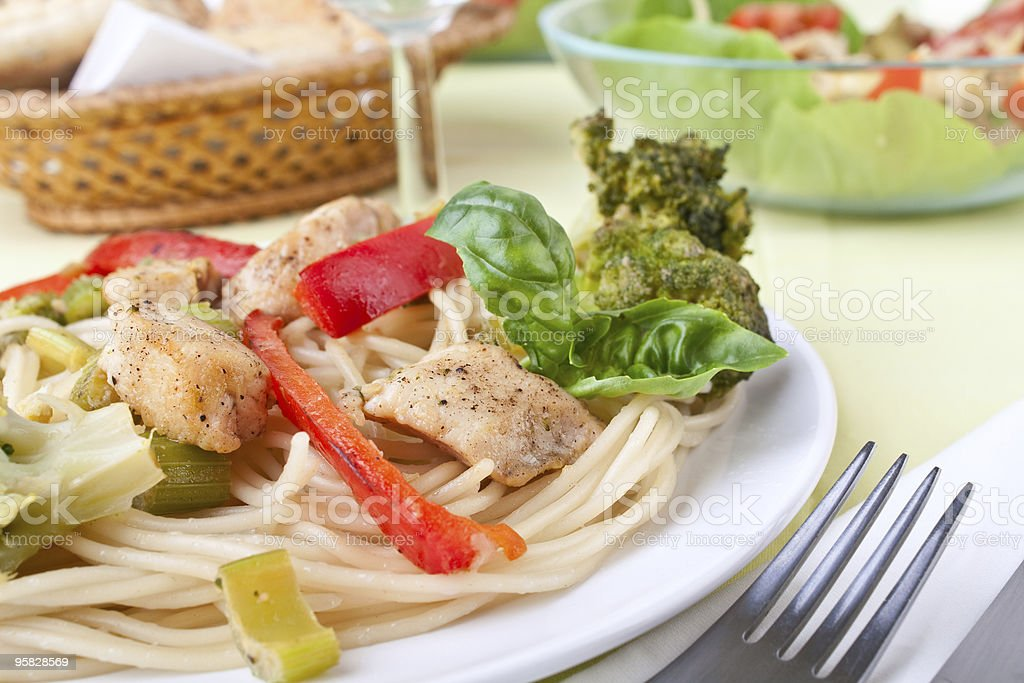 chicken and broccoli pasta  with salad at the back royalty-free stock photo