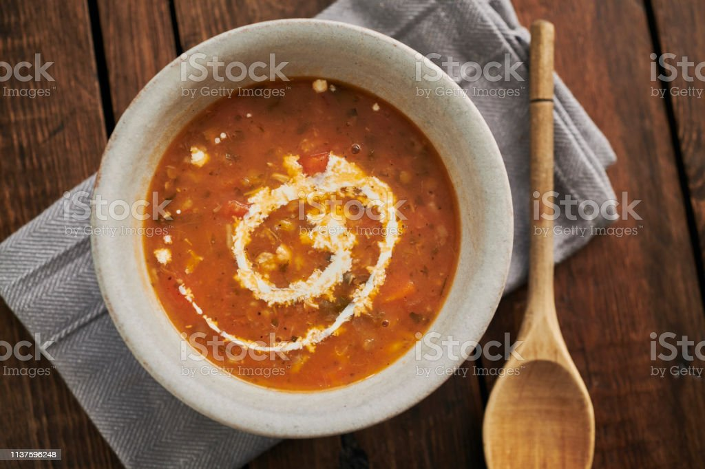 Chicken and mixed grain soup topped with a swirl of cream. stock photo