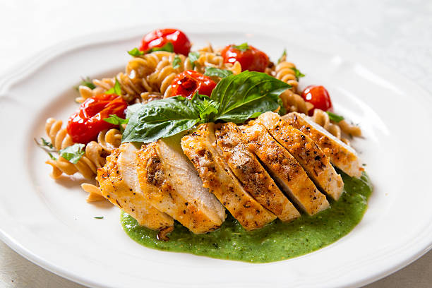 Chicken and pasta with pesto cream sauce stock photo