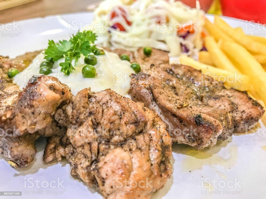 Chicken and pork steak on white plate stock photo