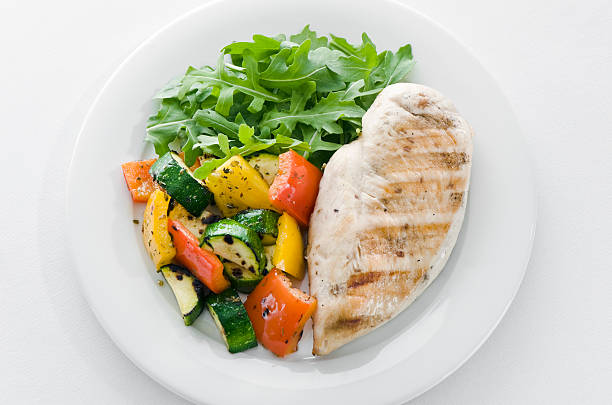 Chicken and roasted veg with lettuce on white plate stock photo