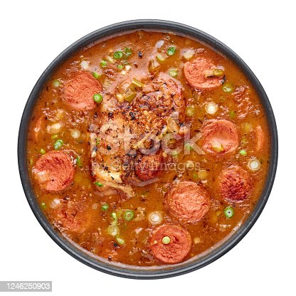 Chicken and Sausage Gumbo soup in black bowl isolated on white backdrop. Gumbo is louisiana cajun cuisine soup with roux. American USA Food. Traditional ethnic meal