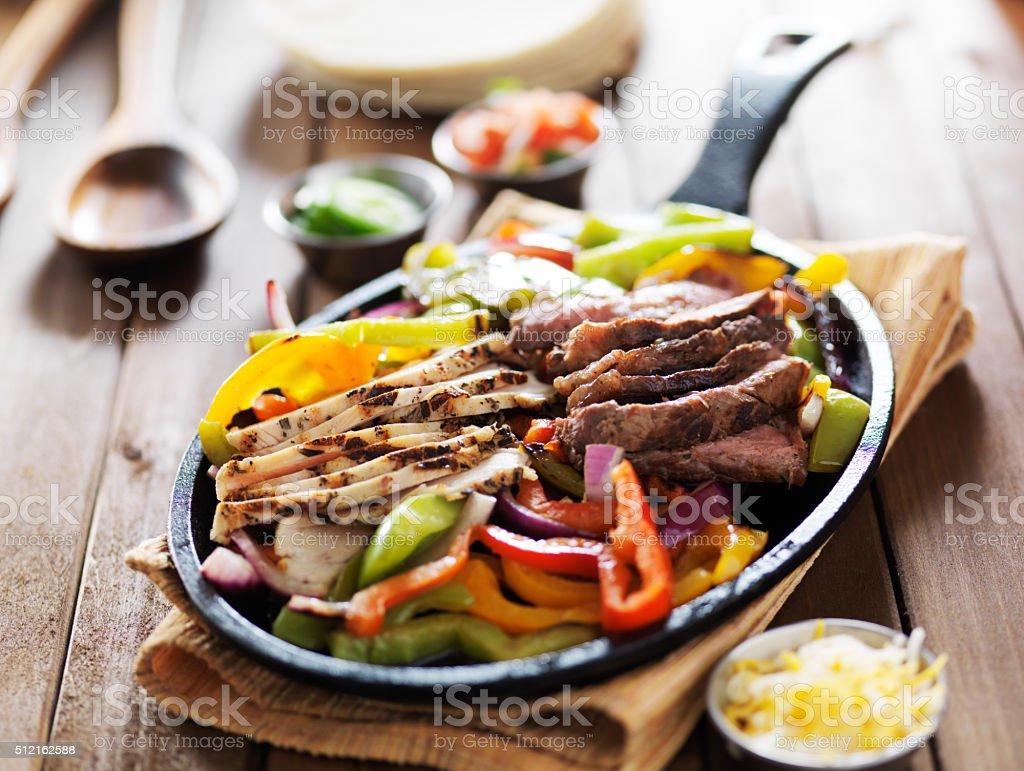 chicken and steak mexican fajitas in iron skillet stock photo
