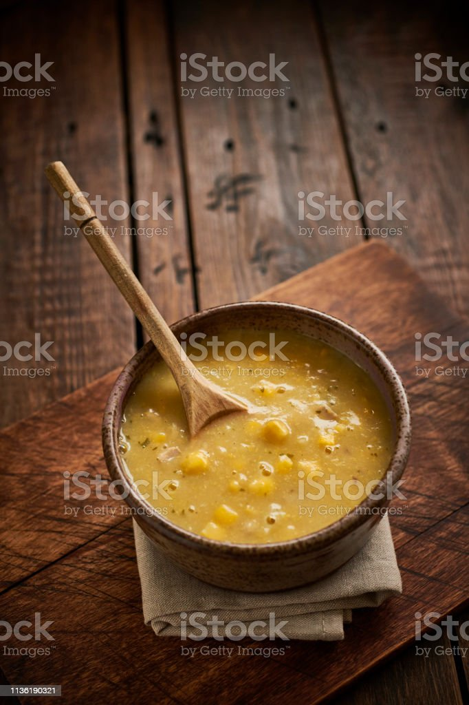 Chicken and sweetcorn soup in a rustic bowl on a dark aged wood table top. stock photo