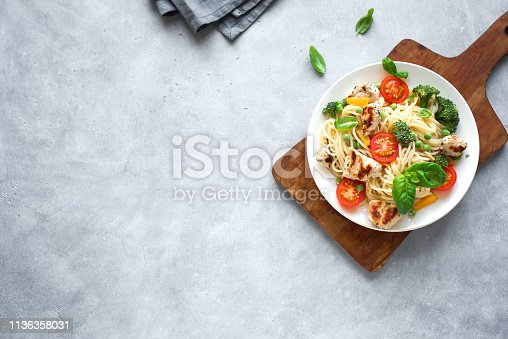 Chicken and Vegetables Pasta. Spaghetti pasta with grilled chicken meat, vegetables and basil, top view, copy space. Seasonal pasta primavera recipe.