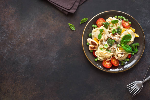 Chicken and Vegetables Pasta Chicken and Vegetables Pasta. Spaghetti pasta with grilled chicken meat, vegetables and basil, top view, copy space. Seasonal pasta primavera recipe. primavera stock pictures, royalty-free photos & images