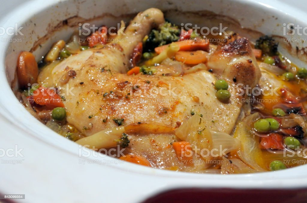 Chicken and vegetables slow cooking in a stoneware stock photo