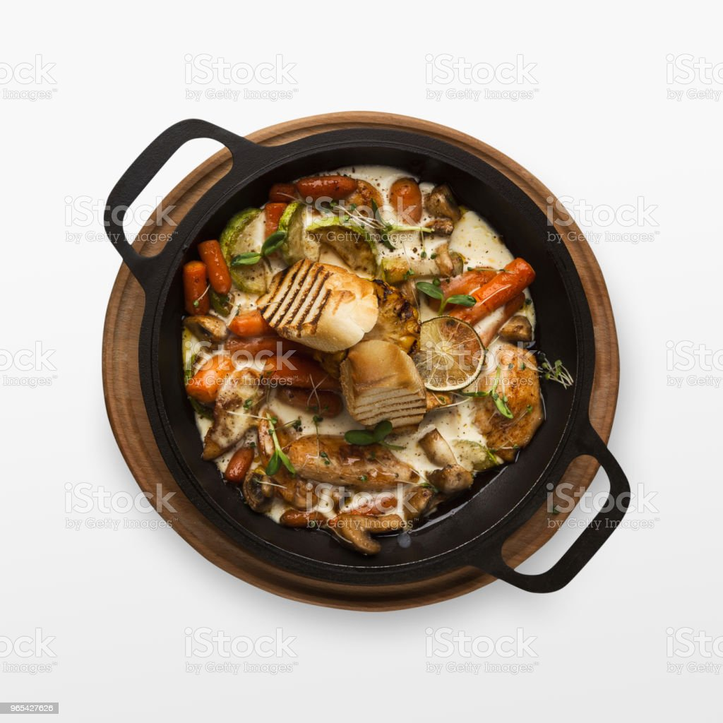 Chicken and vegetables stewed in pot, isolated on white royalty-free stock photo