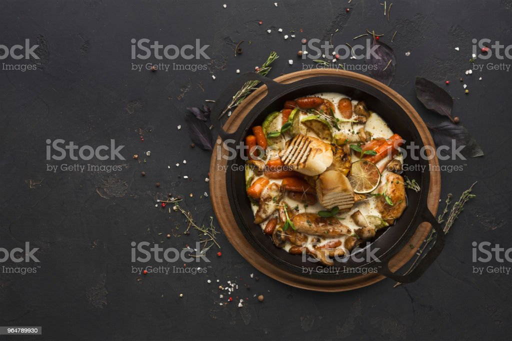 Chicken and vegetables stewed in pot on black background royalty-free stock photo