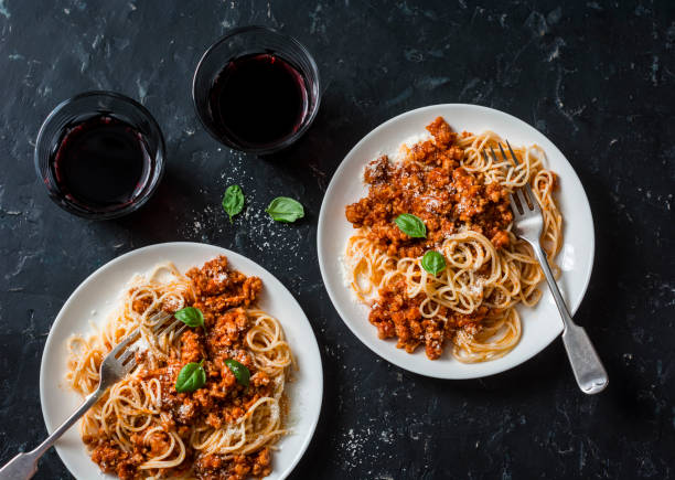 Chicken bolognese spaghetti and glasses of red wine on dark background, top view. Delicious lunch in a mediterranean style, top view. Flat lay stock photo