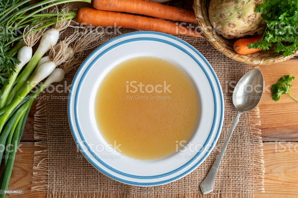 Chicken bone broth in a plate with vegetables stock photo