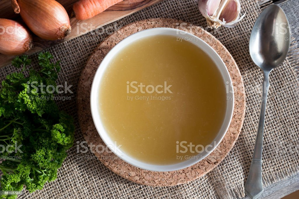 Chicken bone broth with vegetables in the background, top view stock photo