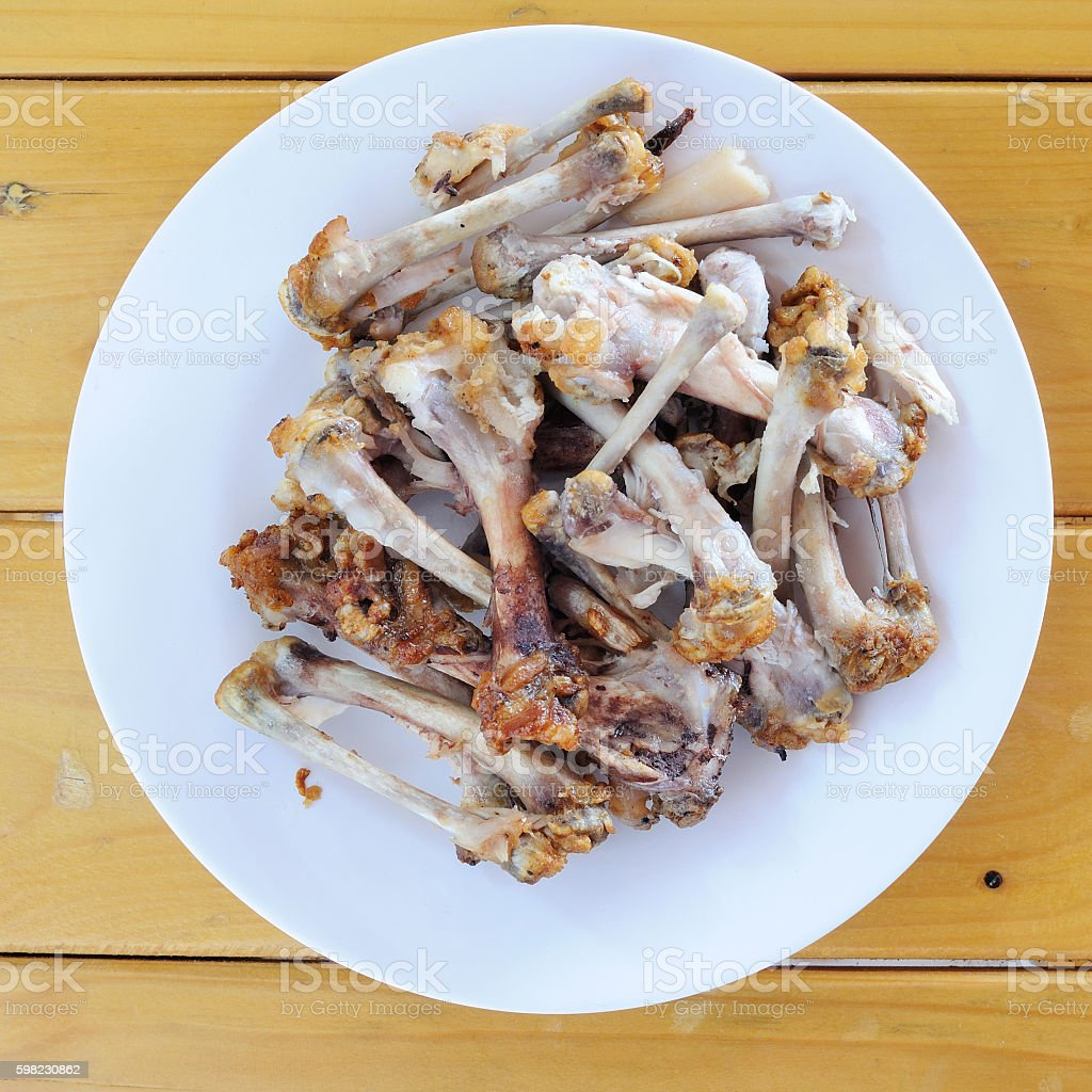 Chicken bones in white plate on wooden table, food scraps foto royalty-free