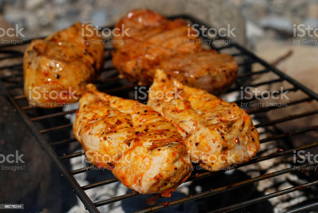 Chicken breast and steacks grilled on a natural fire pit royalty-free stock photo