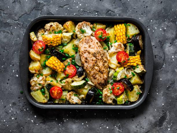 kycklingbröst bakat med potatis, blomkål, majs, aubergine, zucchini, körsbärstomater på en plåt på en mörk bakgrund, uppifrån. hälsosam matkoncept - bakplåt bildbanksfoton och bilder