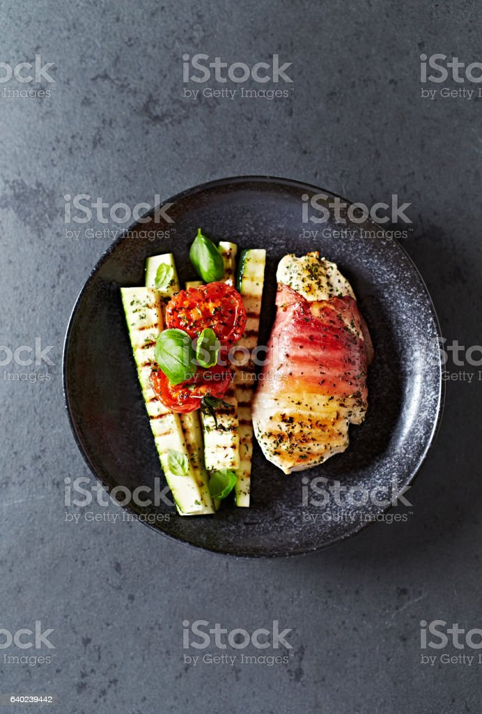 Chicken breast wrapped in ham with grilled zucchini and tomatoes stock photo