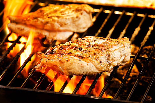 Chicken breasts grilling over an open flame stock photo