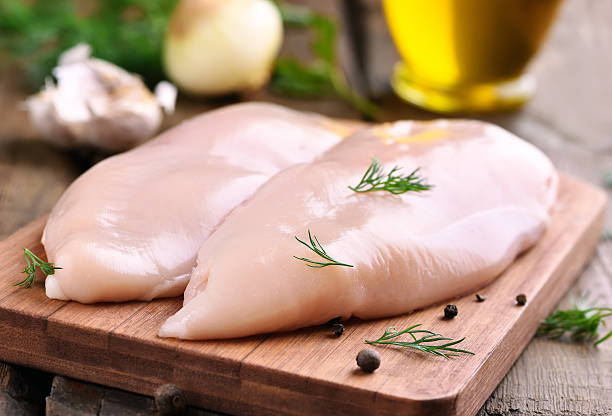 Chicken breasts on cutting board Raw chicken breasts and spices on wooden cutting board, close up view poultry stock pictures, royalty-free photos & images