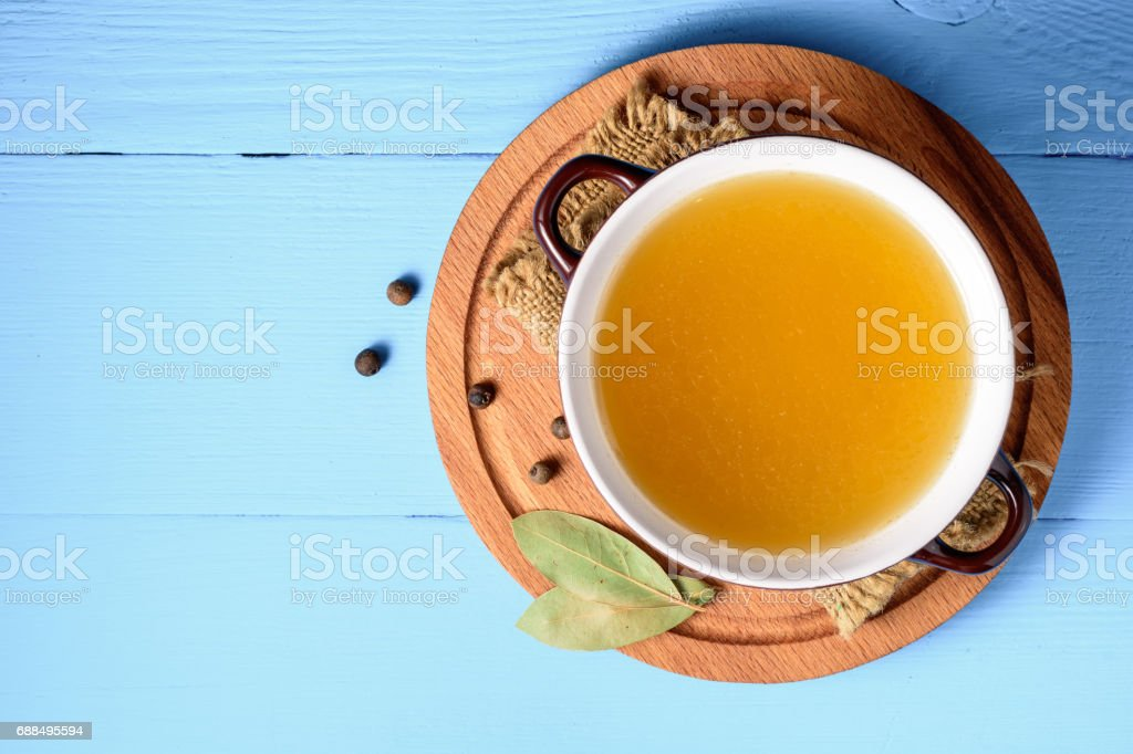 Chicken broth in ceramic bowl on blue wooden background. stock photo