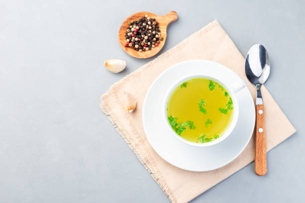 Chicken broth in white cup garnished with chopped parsley, horizontal, top view, copy space stock photo