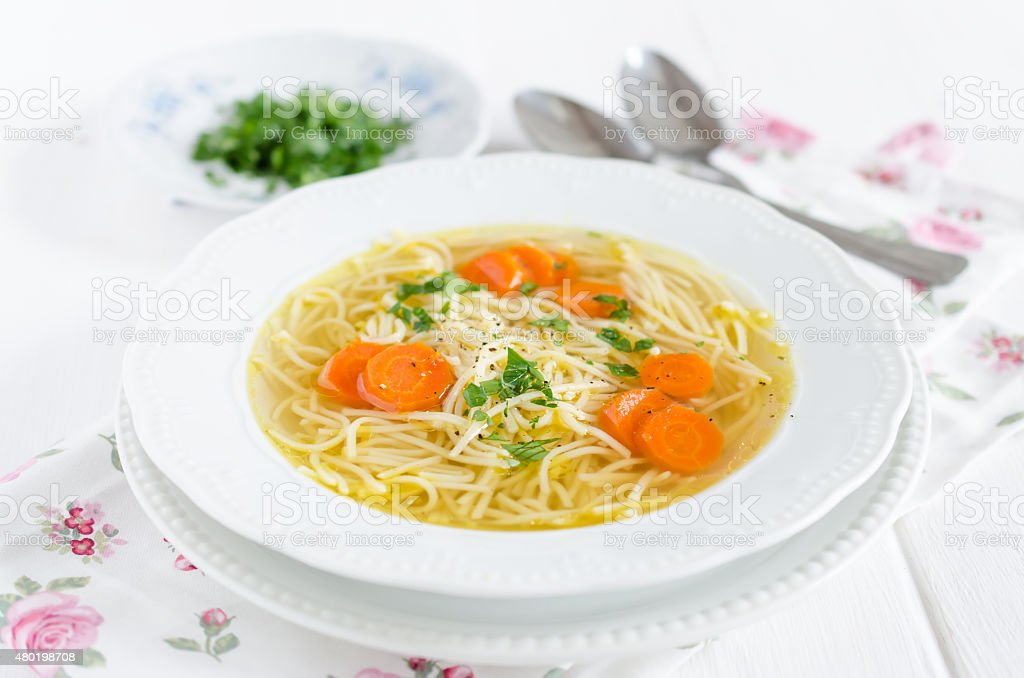 Chicken broth with noodles and carrot stock photo