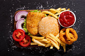 istock chicken burger with french fries and onion rings, top view 865791350