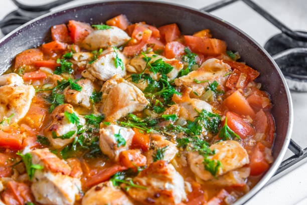 Chicken cacciatore is cooked in a frying pan, chicken stew with tomatoes and red pepper - top view Chicken cacciatore is cooked in a frying pan, chicken stew with tomatoes and red pepper - top view stew stock pictures, royalty-free photos & images