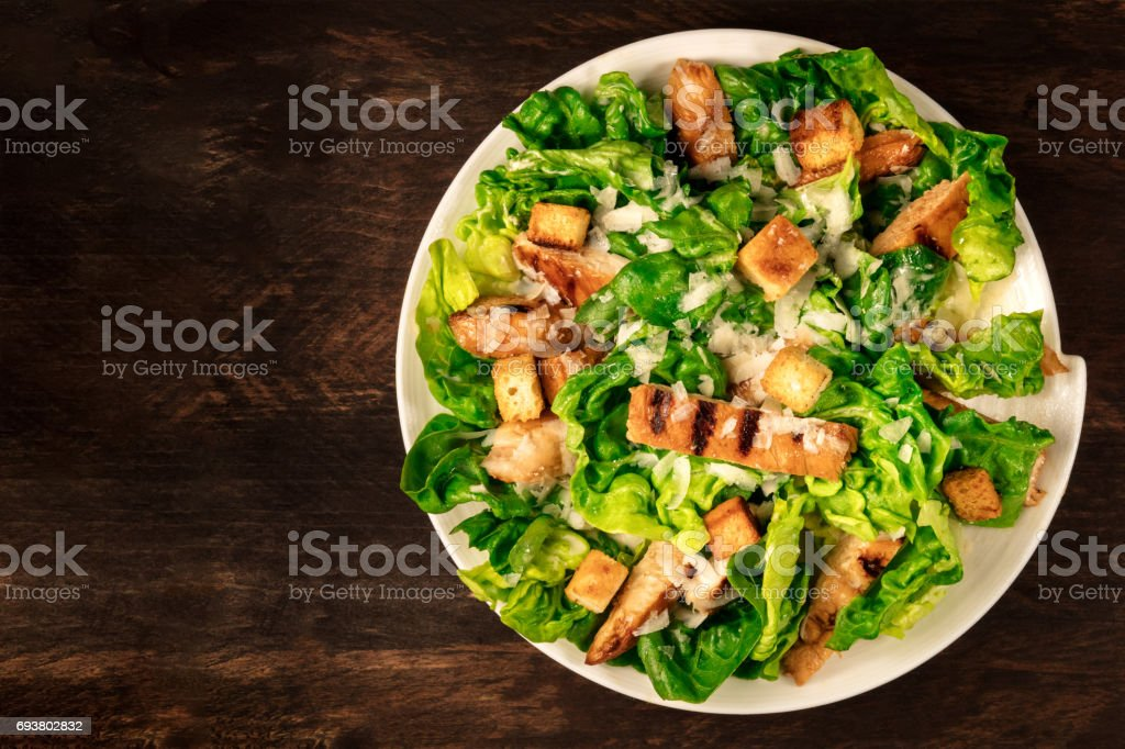 Chicken Caesar salad on rustic background with copyspace stock photo