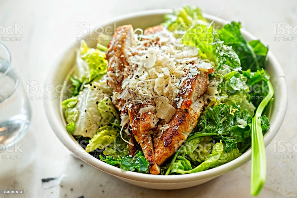 Chicken Ceasar salad. Cos lettuce leaves, grilled chicken breast sliced, parmesan cheese. Restaurant table. stock photo