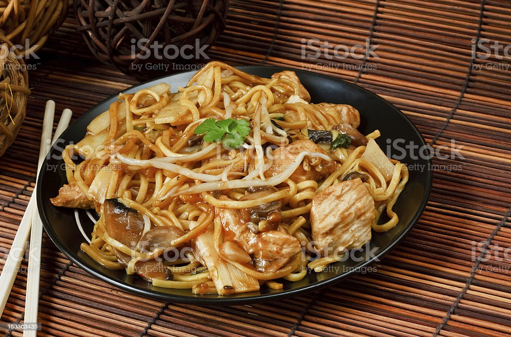 Chicken chow mein on bamboo mat with chopsticks stock photo