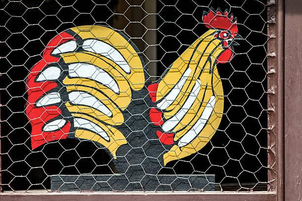hühnerstall mit einem dekorativen hölzernen painted hahn hinter mesh - lustiges huhn bilder stock-fotos und bilder